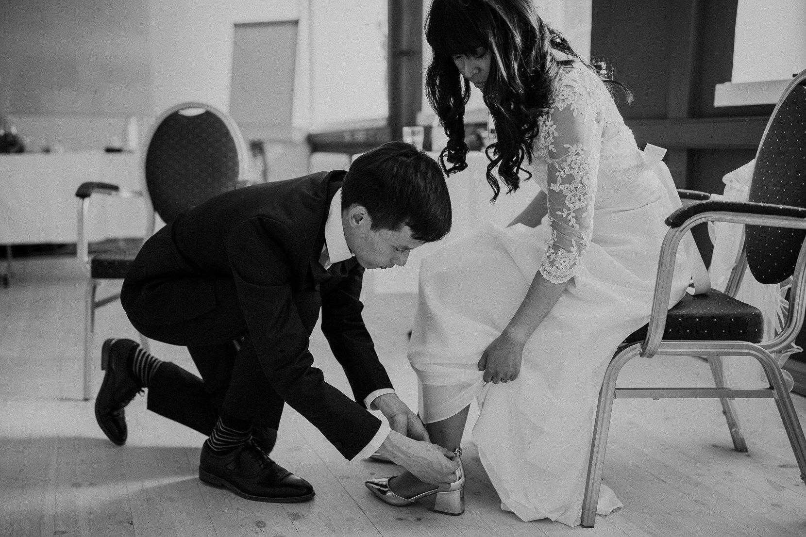 Brudgum hjälper med brudens skor